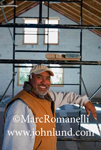 Portrait of an Hispanic Worker On a Construction Site. He is leaning on scaffolding inside a new building under construction. He is smiling.